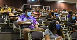 students seated socially distant in a classroom wearing masks